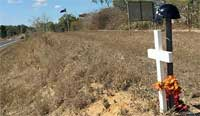 A black hat and white cross marks the spot where Susanne Caudell lost her life on the Bruce Highway